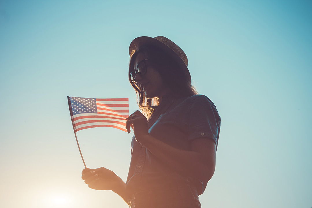 Woman holding USA flag against the blue sky. Celebrating Independence Day of America